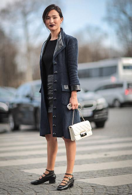Девушка в мини юбке, топ и серое пальто на пуговицах, белая сумочка