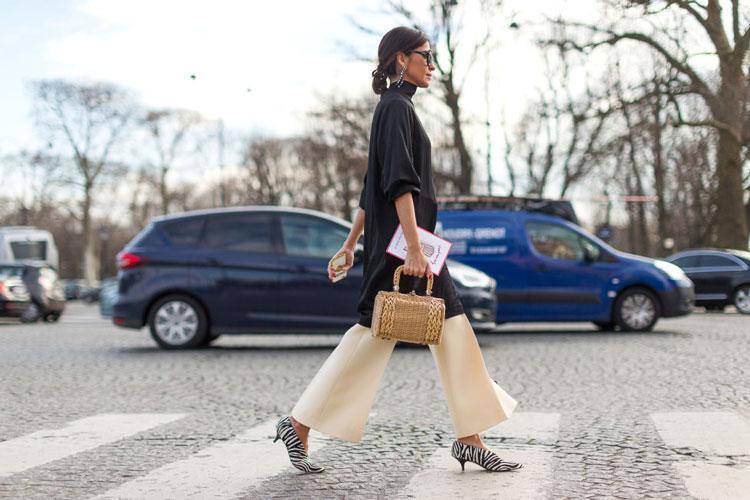 Девушка в молочных брюках клеш, черная туника и туфли на маленьком каблуке с принт ом зебра
