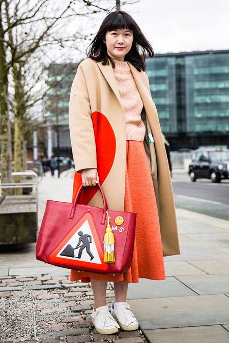Девушка в оранжевой юбке миди, свиншот и бежевое пальто с оранжевыми вставками, большая красная сумка, неделя моды - Лондон осень/зима 2016-2017