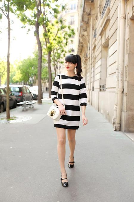 Девушка в полосатом черно-белом платье, маленькая сумочка
