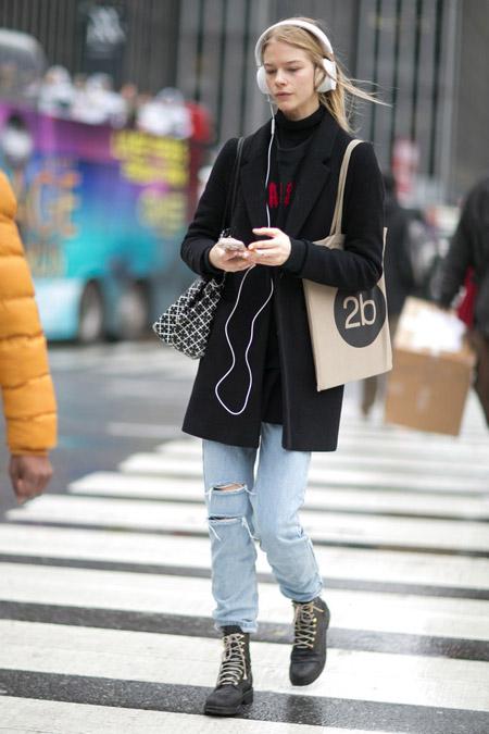 Девушка в рванных джинсах. ботинках на шнуровке и черном пальто пямого кроя