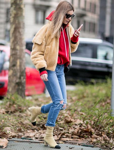 Девушка в рваных джинсах, красная олимпийка и меховая курточка