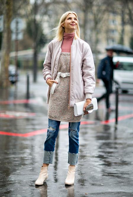 Девушка в рваных джинсах, розовая водолазка, туника и куртка, светлые ботильоны и клатч