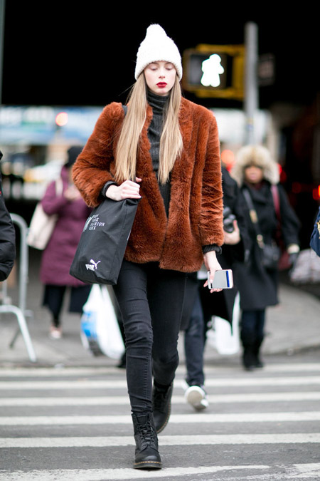 Девушка в серых джинсах, черной водолазке, шапка и коричневая шубка
