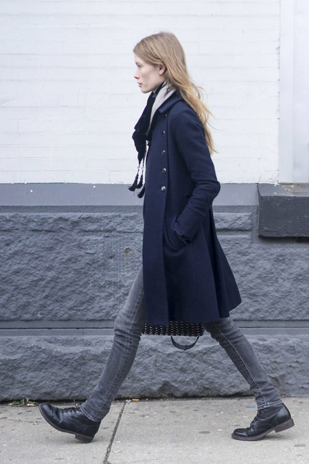 Девушка в серых джинсах, черные ботинки и пальто