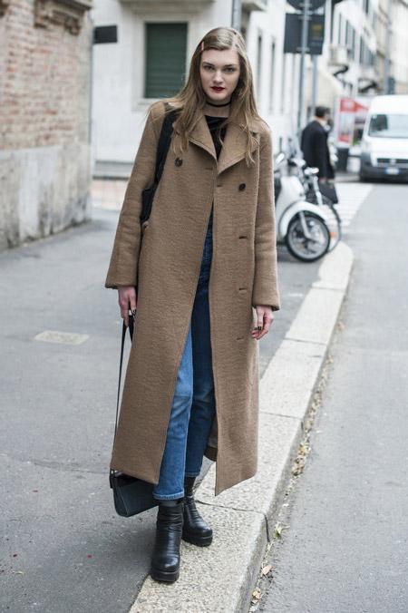 Девушка в синих джинсах и длинном коричневом пальто