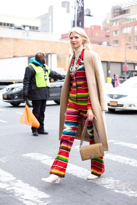 Девушка в ярком брючном костюме, длинном светлом пальто и сумочка