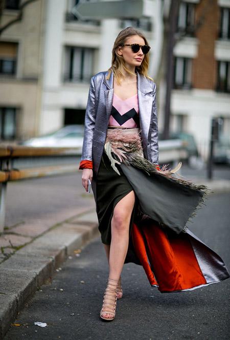 Девушка в юбке, розовый топ и серебристый длинный плащ
