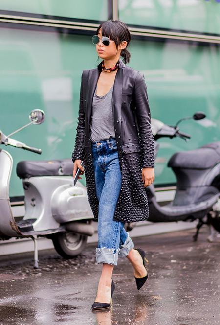 Девушка в закатанных джинсах прямого покроя, футболка и кожанный плащ