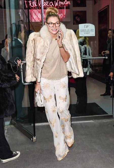 Джессика Харт в белых брюках с бабочками, светлая блузка и шубка