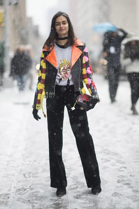 Gizele Oliveira в черных брюках, футболка с принтом и разноцветная кожанная куртка