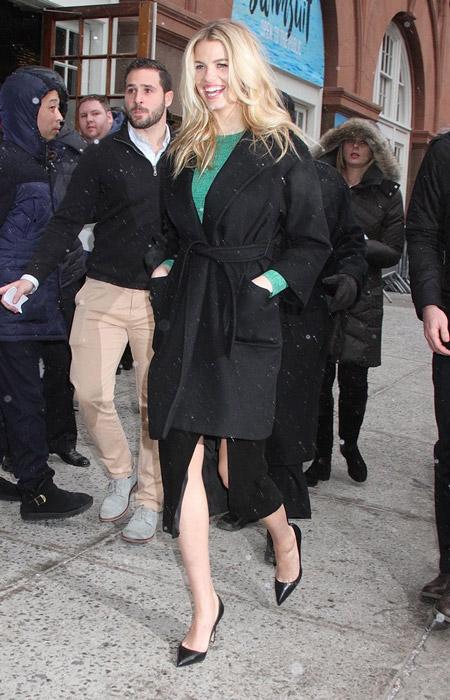 Hailey Clauson в черной юбке с разрезом, зеленая кофточка и черное пальто с поясом