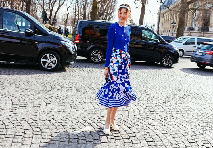 Irene Kim в синей юбке миди с белым принтом, синий кардиган и белые туфли