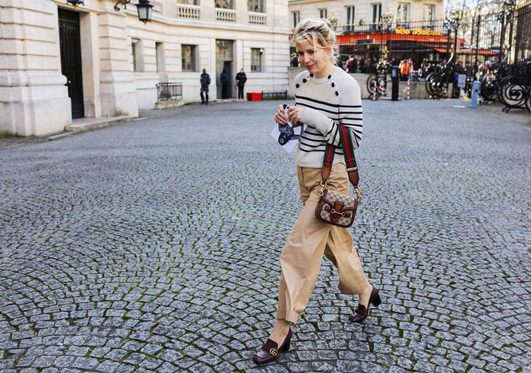 Julia von Boehm в светлых брюках, серая кофточка в полоску, кричневые туфли и сумочка