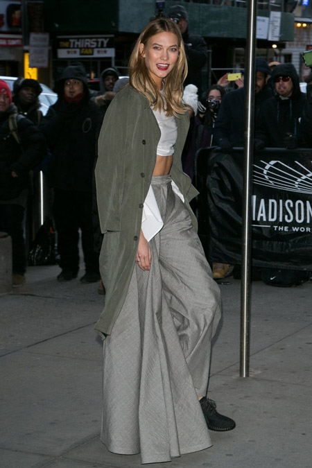 Карли Клосс в очень широких серых брюках, кроп топ и серый плащ