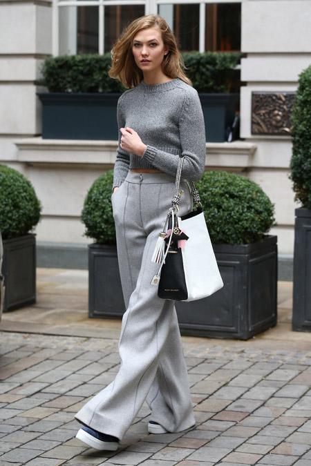 Карли Клосс в серых широких брюках, обрезаном свитере, черно белая сумка и кеды на платформе, неделя моды - Лондон осень/зима 2016-2017