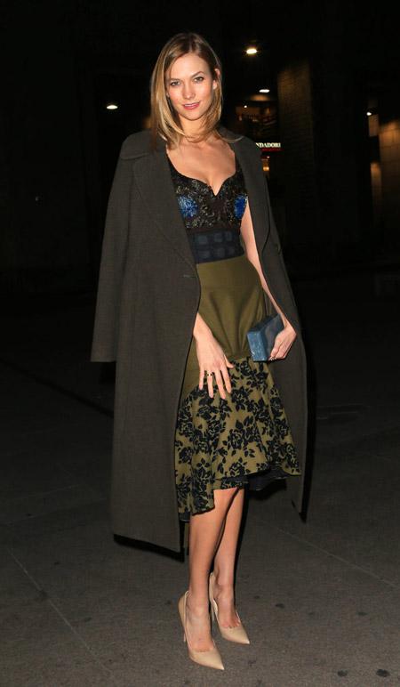 Карли Клосс в темной юбке с черным принтом, топ и серое пальто