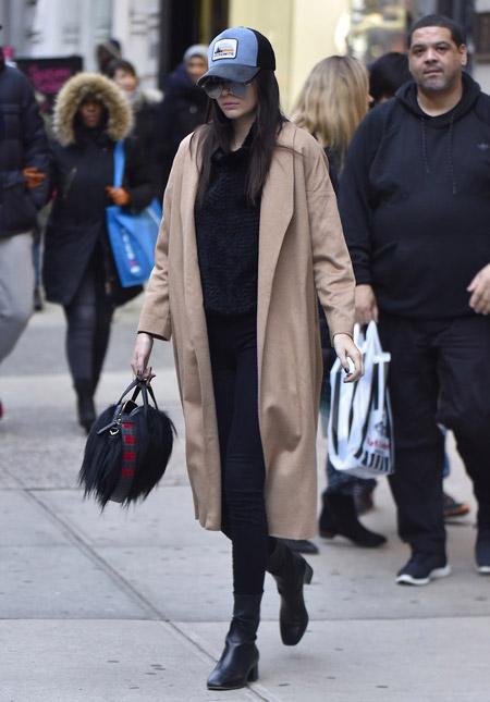 Кендалл Дже́ннер в черных брюказ, меховая сумочка и бежевый плащ