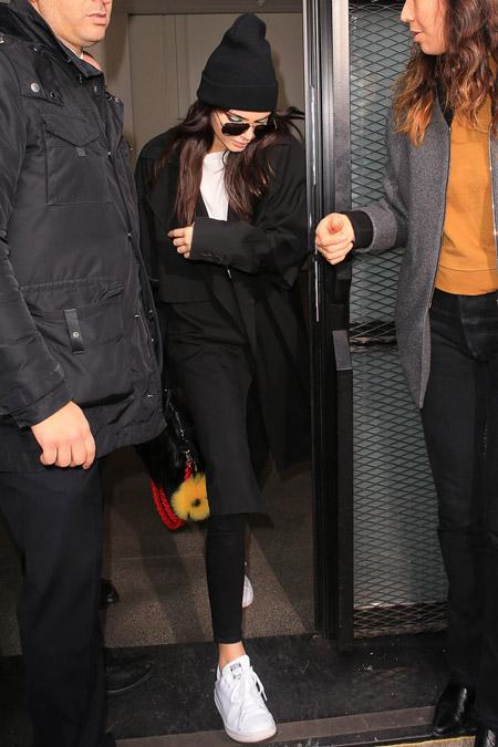 Кендалл Дженнер в черном плаще, лосинах, белой футболке и кроссовках