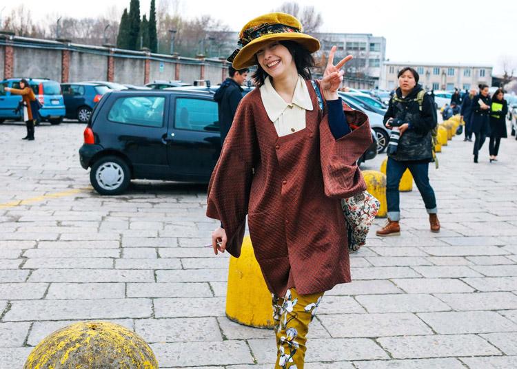 Mae Lapres в желтых брюках с принтом и бордовом пальто, шляпка