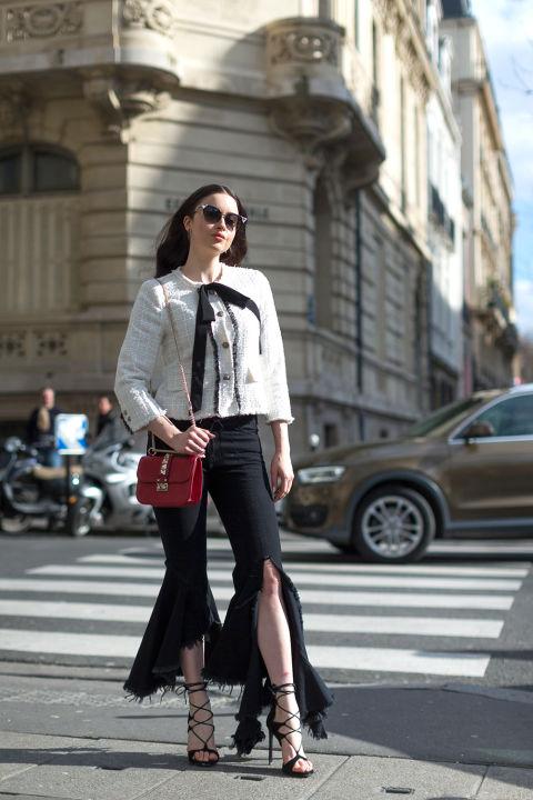 Девушка в черных брюках с разрезом спереди от Marques Almeida, светлый жакет и босоножки