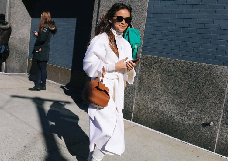 Miroslava Duma в белом пальто, водолазке и коричневой сумочкой