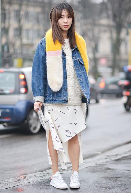 Модель в белой юбке с черными полосками, белом свиншоте и джинсовой куртке, шарф