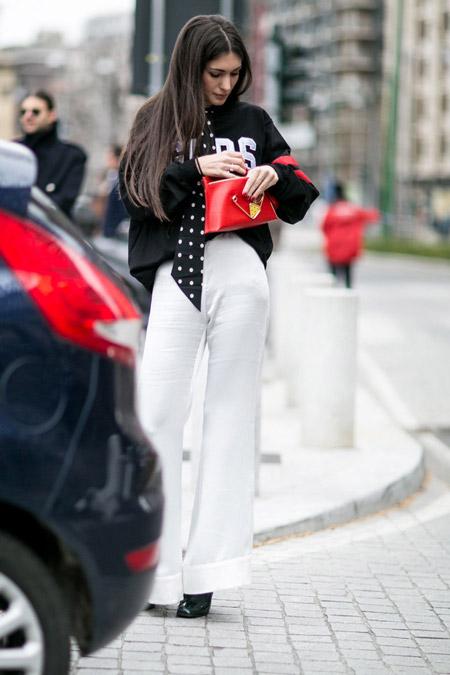 Модель в белых брюках и черном свиншоте