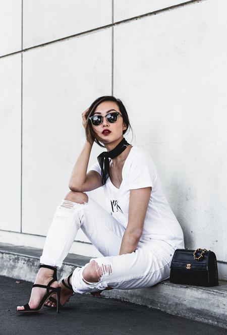 Модель в белых рваных брюках, футболка, босоножки