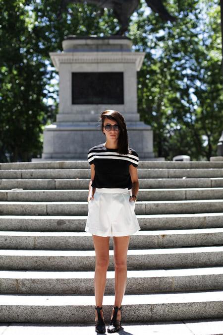 Модель в белых шортах и черной футболке с полосками