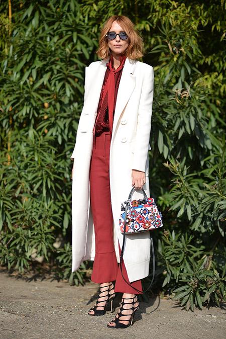 Модель в бордовых капри, блузе и белое пальто