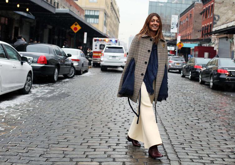 Модель в брюках молочного цвета, и пальто в клетку