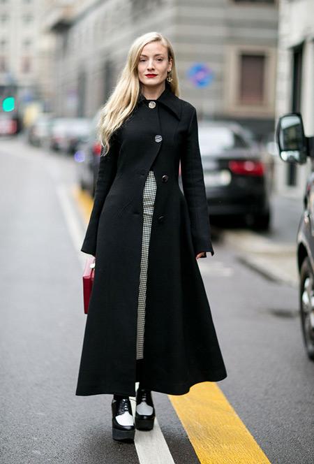 Модель в черном длинном пальто и ботинках на высокой платформе