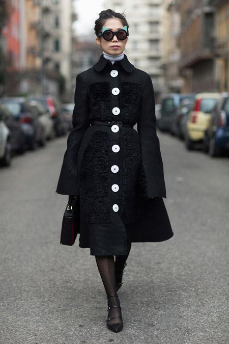 Модель в черном классическом пальто в белыми пуговицами