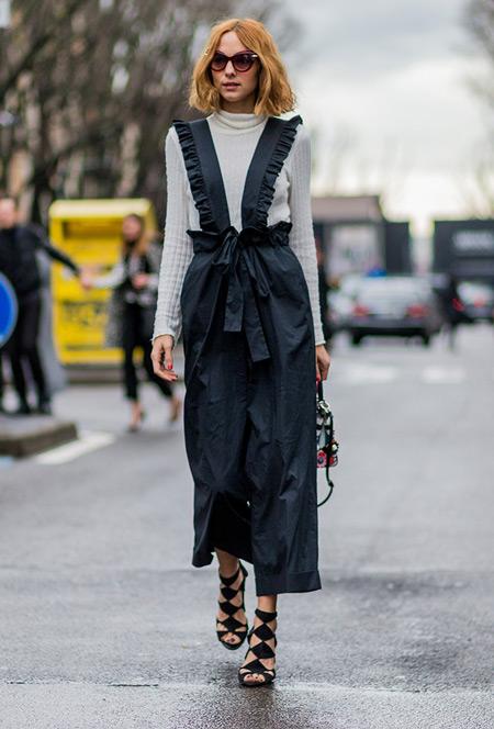 Модель в черном комбинезоне с рюшами и серой водолазке, черные босоножки
