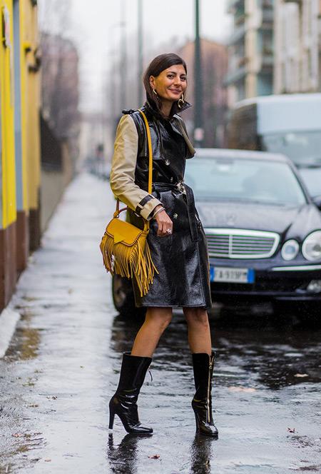 Модель в черном кожанном плаще с бежевыми рукавами, сапоги и желтая сумочка с бахромой