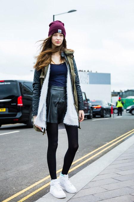 Модель в черной кожаной юбке, топ, белые кроссовки, неделя моды - Лондон осень/зима 2016-2017