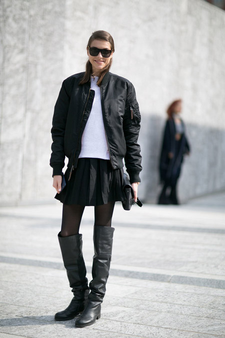 Модель в черной мини юбке и куртке, сапоги выше колена и куртка