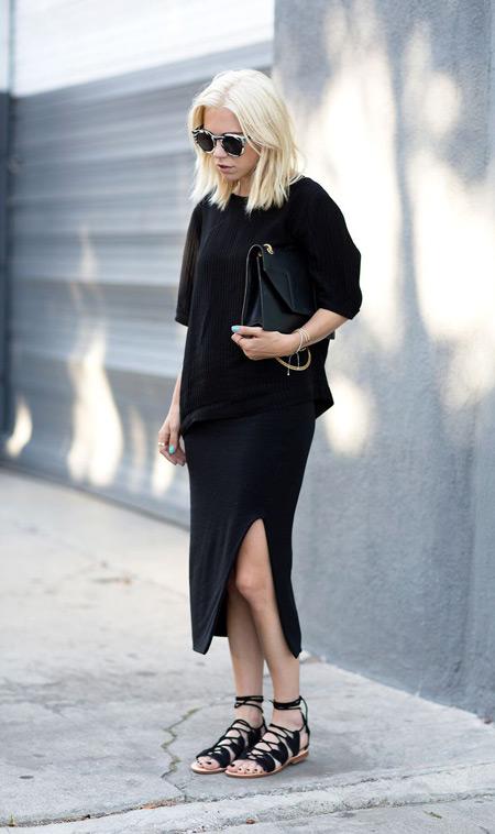 Модель в черной юбке с разрезом, свиншот и черные сандалии и сумочка