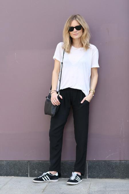 Модель в черных брюках, белая футболка и кеды