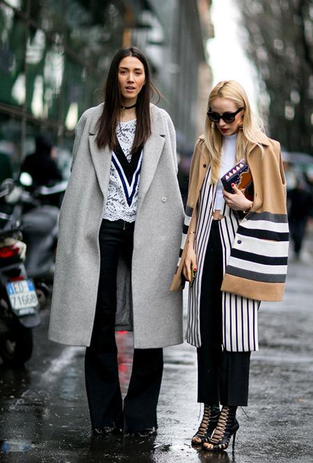Модель в черных брюках, блузке и светло сером пальто, модель в черных капри, белом кардигане с черными полосками