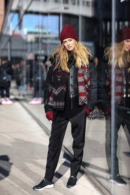 Модель в черных брюках, черном свитере, куртке и бордовой шапке