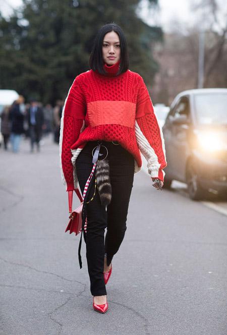 Модель в черных брюках и красно белом свитере