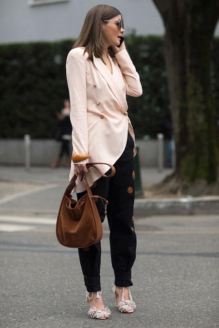 Модель в черных брюках и нежно розовом кардигане, замшевая сумка