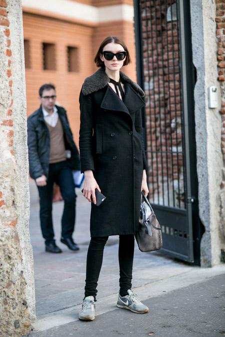 Модель в черных брюках скини и пальто, кроссовки