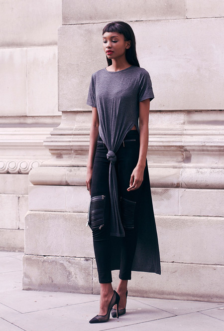 Модель в черных лосинах, серой тунике и туфлях