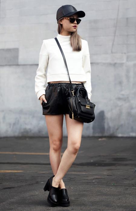 Модель в черных мини шортах, белая кофта, кепка, лоферы