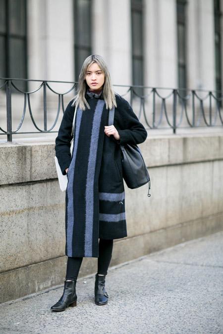 Модель в черных скинни и пальто с серыми полосками