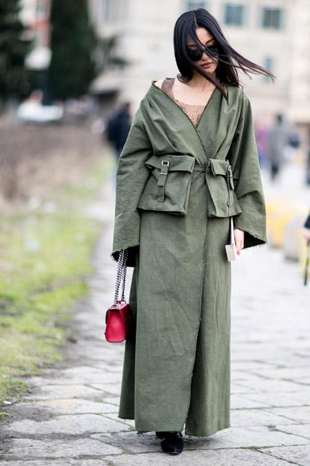 Модель в длинном плаще с накладными карманами и маленькая розовая сумочка