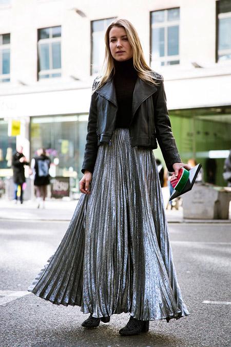 Модель в длинной плиссированой юбке, черной водолазке и куртке косухе, неделя моды - Лондон осень/зима 2016-2017